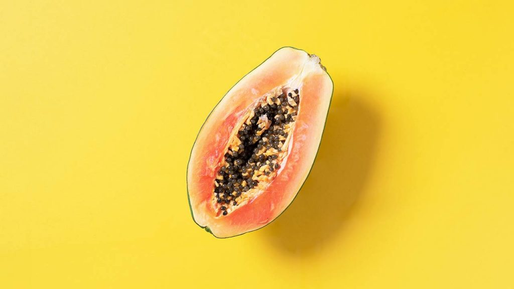 Halved papaya on yellow background