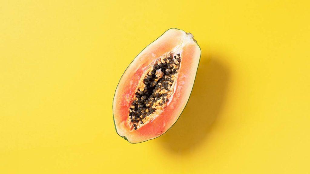 Halved papaya on yellow background