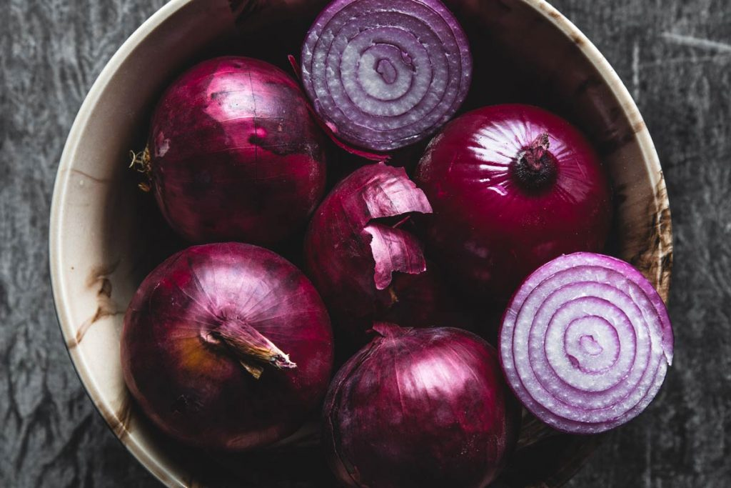 Plate with purple onion. Onions with water droplets. On the table scattered onion husk